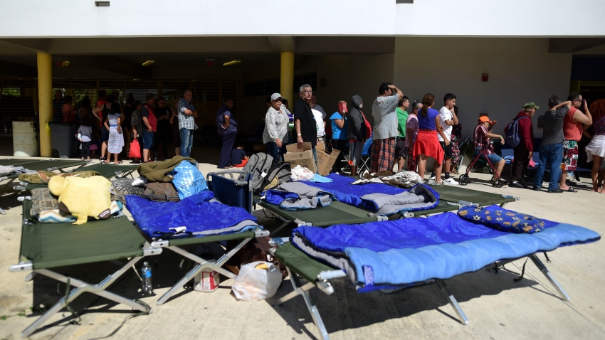 People whose homes are unsafe to enter after the previous day's magnitude 6.4 earthquake line up for lunch in an outdoor area of the Bernardino Cordero Bernard High School in Ponce, Puerto Rico, Wednesday, Jan. 8, 2020.