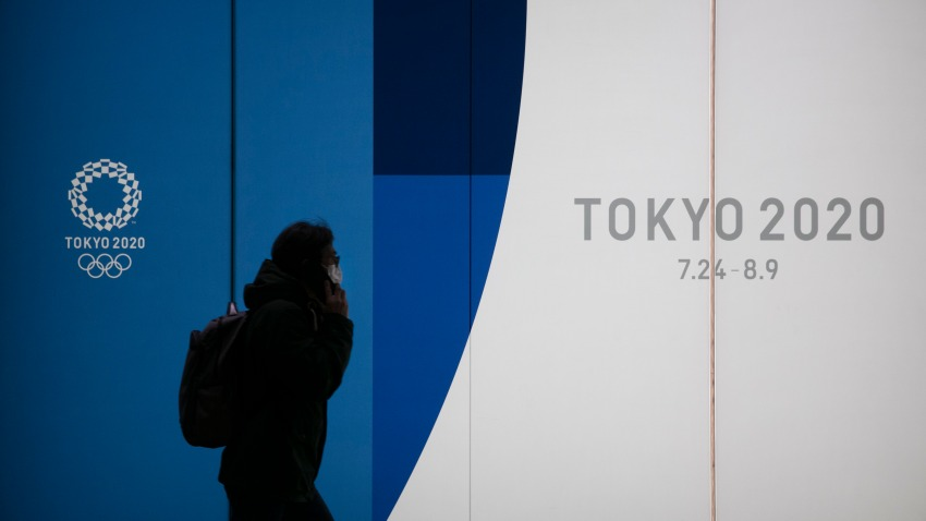 A man with a mask walks past a display promoting the Tokyo 2020 Olympics Monday, Feb. 24, 2020, in Tokyo. (AP Photo/Jae C. Hong)