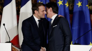 Emmanuel Macron, left, puts his arm around the shoulder of Italian Premier Giuseppe Conte and gives him a kiss on both cheeks.