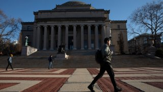 In this March 9, 2020, file photo, a man walks past Low Library on the Columbia University campus in New York.