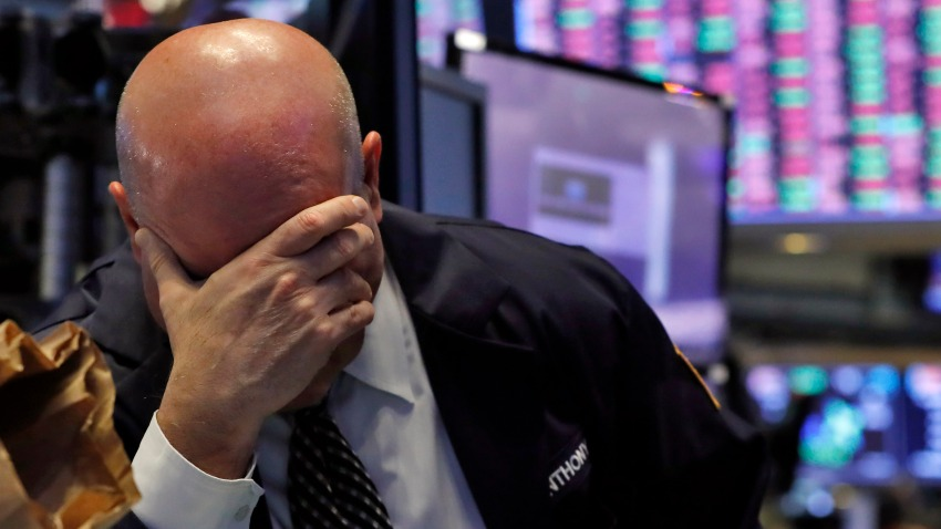 In this March 12, 2020, file photo, a trader has his head in his hand on the floor of the New York Stock Exchange.