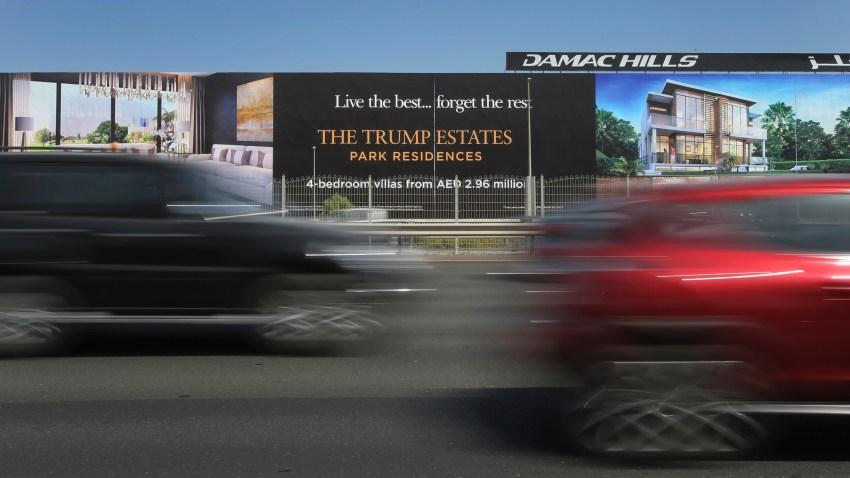 cars pass a giant billboard adverting DAMAC Properties' Trump Estates golf course villas in Dubai