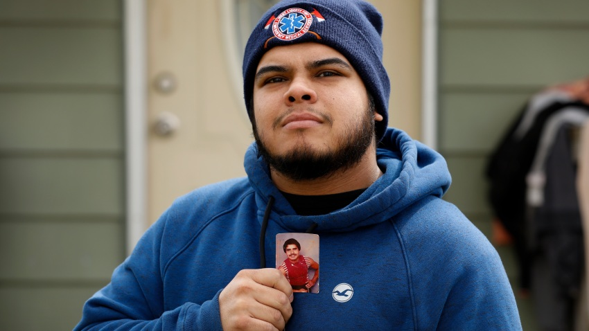 Omar Martinez holds a photo of his father, Jose Gabriel Martinez, as he stands in front of their home