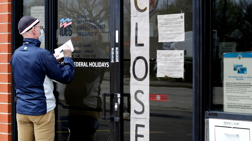 In this April 30, 2020 file photo, a man writes information in front of Illinois Department of Employment Security in Chicago. U.S. businesses cut an unprecedented 20.2 million jobs in April, an epic collapse with coronavirus outbreak closing the offices, factories, schools, construction sites and stores that propel the U.S. economy. The Wednesday, May 6, report from payroll company ADP showed the tragic depth and scale of job losses that left no part of the world's largest economy unscathed.