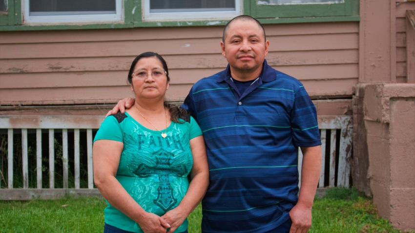 In this photo provided by Cristobal Francisquez, his parents Paulina and Marcos Francisco pose for a photo in front of their house in Sioux City, Iowa, Monday, May 25, 2020. They bought the home after years of working in a meatpacking plant and other food processing jobs.