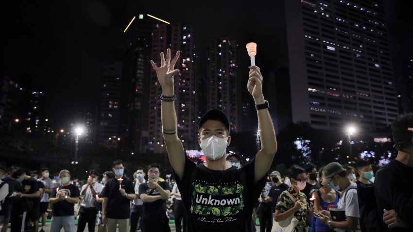 """Participants gesture with five fingers, signifying the """"Five demands - not one less"""" during a vigil for the victims of the 1989 Tiananmen Square Massacre at Victoria Park in Causeway Bay, Hong Kong, Thursday, June 4, 2020. China is tightening controls over dissidents while pro-democracy activists in Hong Kong and elsewhere try to mark the 31st anniversary of the crushing of the pro-democracy movement in Beijing's Tiananmen Square."""