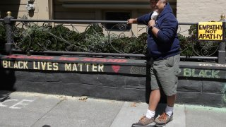 """James Juanillo poses next to chalk written outside of his home in San Francisco, Sunday, June 14, 2020. The CEO of a cosmetic company issued an apology Sunday after she and her husband confronted Juanillo and threatened to call police because he stenciled """"Black Lives Matter"""" in chalk on his San Francisco property, as the couple asserted that they know Juanillo doesn't live there and is therefore breaking the law."""
