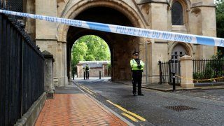 Police stand guard at the Abbey gateway of Forbury Gardens park in Reading town centre following Saturday's stabbing attack in the gardens, Sunday June 21, 2020