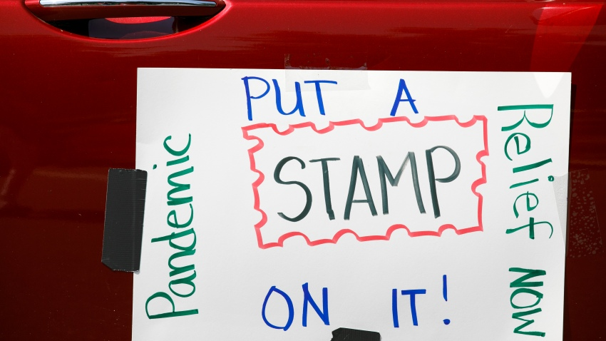 Part of a car caravan of postal employees has a sign on it asking Congress to approve emergency funding for the Postal Service, Tuesday, June 23, 2020, on Capitol Hill in Washington.