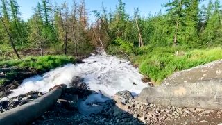 water from a Norilsk Nickel enrichment plant gushing out of a pipe and into a river which also runs into the lake near Norilsk