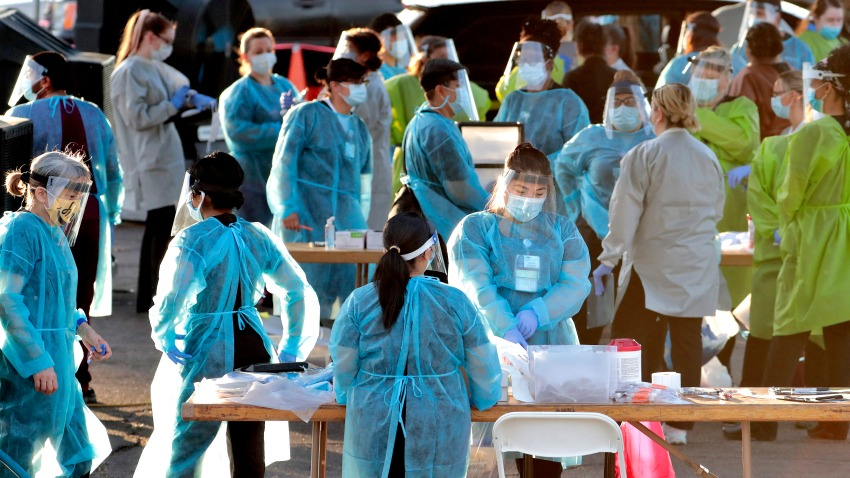 In this June 27, 2020, file photo, medical personnel prepare to test hundreds of people lined up in vehicles in Phoenix's western neighborhood of Maryvale.