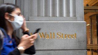 In this June 30, 2020, file photo, a woman wearing a mask passes a sign for Wall Street during the coronavirus pandemic.