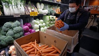 A worker wearing a protective mask stocks produce before the opening of Gus's Community Market, March 27, 2020, in San Francisco.