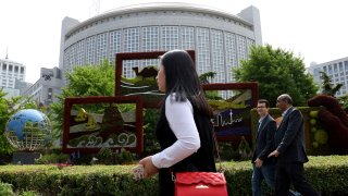 In this April 19, 2019, file photo, foreigners pass by the Chinese Foreign Ministry in Beijing, China.