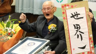 In this Japan Pool picture received via Jiji Press on February 12, 2020, 112-year-old Japanese man Chitetsu Watanabe poses next to calligraphy reading in Japanese 'World Number One' after he was awarded as the world's oldest living male in Joetsu, Niigata prefecture.