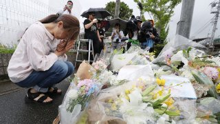 This July 19, 2019 picture shows a resident praying for victims of a fire which hit the Kyoto Animation studio building the day before, killing 37 people, in Kyoto.