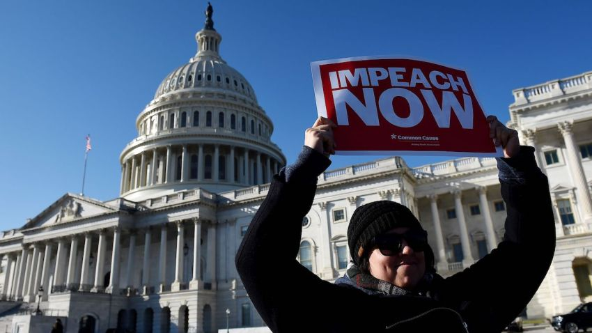 A woman holds a sign during an impeachment rally in front of the U.S. Capitol building on December 18, 2019 in Washington, DC.