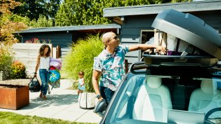 Family loading luggage into car top box before a road trip