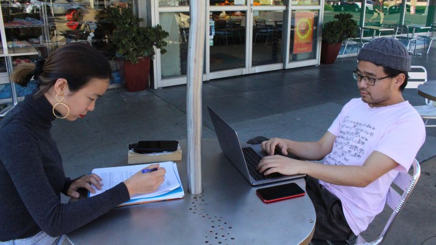 "International students Yaqing ""Victoria"" Yang and Ende Shen of China study together at a sidewalk table in the Silicon Valley city of Palo Alto"