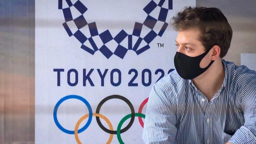 Un hombre con una mascarilla se sienta en una parada de autobús frente a un anuncio de los Juegos Olímpicos de Tokio 2020 en Bangkok este 16 de marzo de 2020.