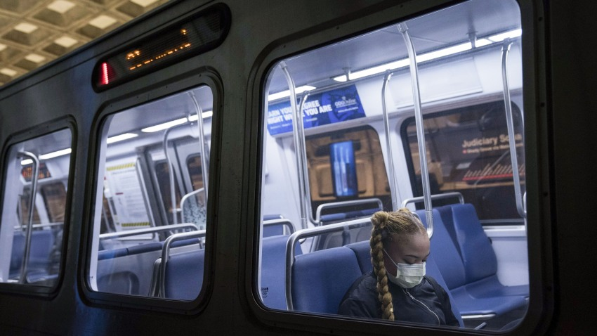 A commuter wears a protective face mask while riding on a subway train in Washington, D.C., U.S., on Monday, March 16, 2020.