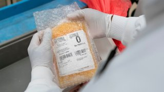 In this April 22, 2020, file photo, a lab technician freezes packs of convalescent plasma donated by recovered COVID-19 patients for shipping to local hospitals at Inova Blood Services in Dulles, Virginia.