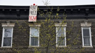 A building tenant hangs a sign from his roof in the Crown Heights neighborhood during a rent strike on May 1, 2020 in New York City.
