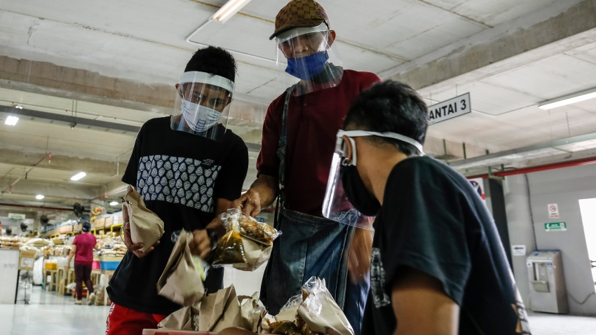 Market merchants wearing face mask and shield as they buy foods amid coronavirus disease (COVID-19) pandemic in Denpasar's traditional market, Bali, Indonesia on May 15 2020.