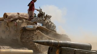 A fighter loyal to Yemen's separatist Southern Transitional Council (STC) stands atop a tank amid clashes with Saudi-backed government forces for control of Zinjibar, the capital of the southern Abyan province, in the Sheikh Salim area on May 23, 2020.