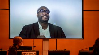 """A TV screen displays George Floyd's brother, Philonise Floyd speaking via video message during an urgent debate on """"systemic racism"""" in the United States and beyond at the Human Rights Council on June 17, 2020 in Geneva."""