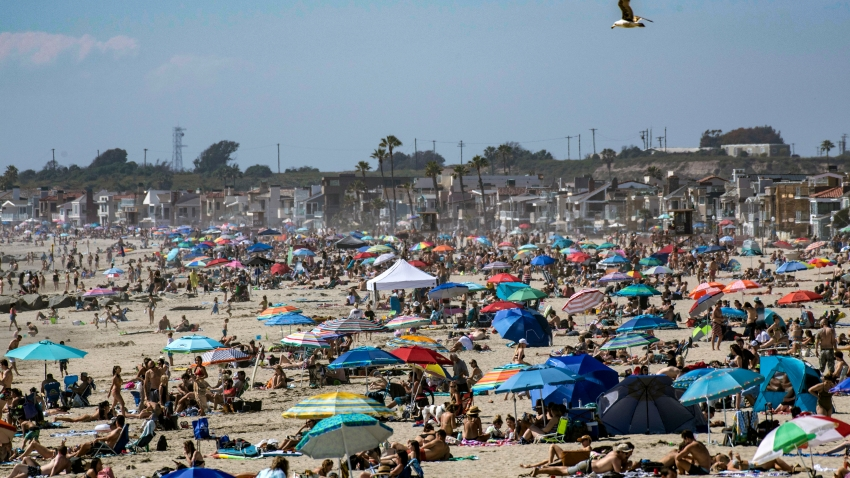 Large crowds gather near the Newport Beach Pier in Newport Beach on Saturday, April 25, 2020 to cool off during the hot weather despite the coronavirus pandemic.