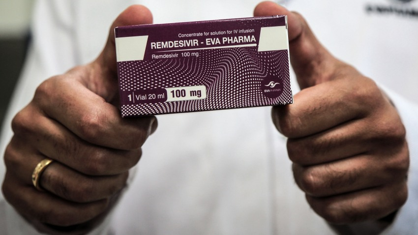 Gloved hands hold a box of coronavirus drug Remdesivir.