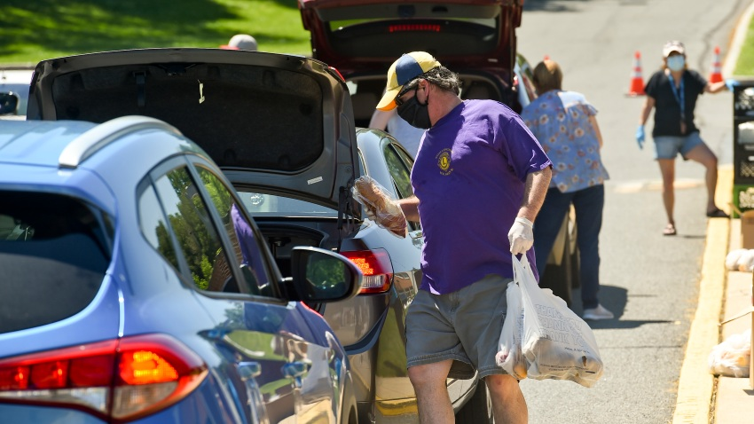 Cumru, PA - May 30: Todd Kaley, with the Shillington Lions Club carries food to a car. During a food distribution by the Wyomissing Restaurant and Bakery, Olivet Boys and Girls Club, Kuhn Funeral Homes and Shillington Lions Club, at the Gov. Mifflin Intermediate School in Cumru Saturday morning May 30, 2020 during the coronavirus / COVID-19 outbreak. People lined up in cars, but they also gave food to people who walked up. (