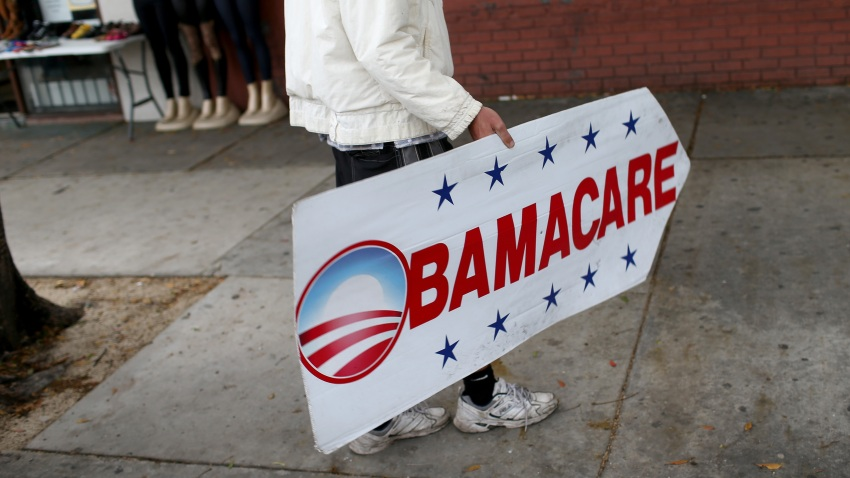 File photo - Pedro Rojas holds a sign directing people to an insurance company where they can sign up for the Affordable Care Act, on Feb. 5, 2015, in Miami, Florida.