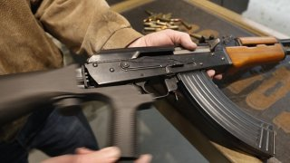 A bump stock is installed on an AK-47 and its movement is demonstrated at a gun range.
