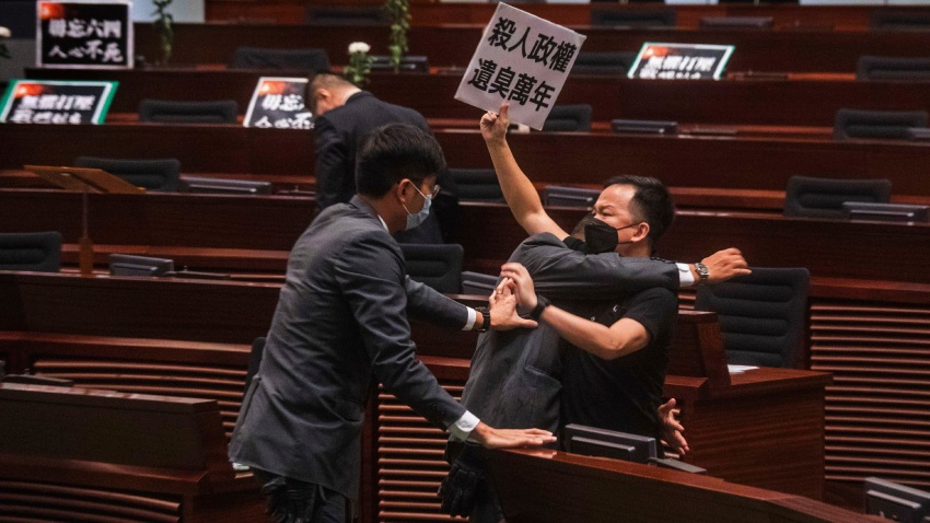 """Pan-democratic legislator Chan Chi-chuen holding a placard reading """"A murderous regime stinks for ten thousand years"""" scuffles with security guards at the main chamber of the Legislative Council dropping a pot of a pungent liquid in the chamber in Hong Kong, Thursday, June 4, 2020."""