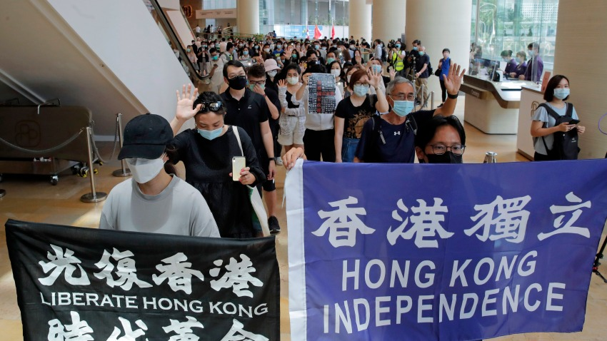 Protesters hold flags in a shopping mall during a protest in Hong Kong, Friday, June 12, 2020. Protesters in Hong Kong got its government to withdraw extradition legislation last year, but now they're getting a more dreaded national security law.