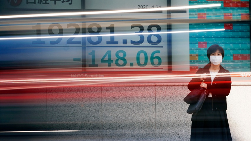 In this April 24, 2020, file photo, a woman wearing a mask to help stop the spread of the new coronavirus stands near an electronic stock board showing Japan's Nikkei 225 index at a securities firm in Tokyo.