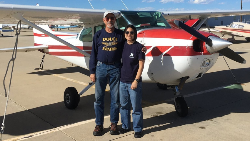 A picture of Joyce Lin in front of a light plane taken from her Facebook page.