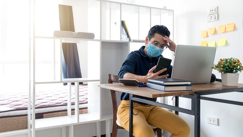 Concentrated Businessman ware mask sitting on working table and looking at Smart phone. Man working from home during corona virus quarantine.
