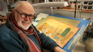 In this file photo taken Sunday Dec. 1, 2013, Tomie DePaola poses with his artwork in his studio in New London, N.H.