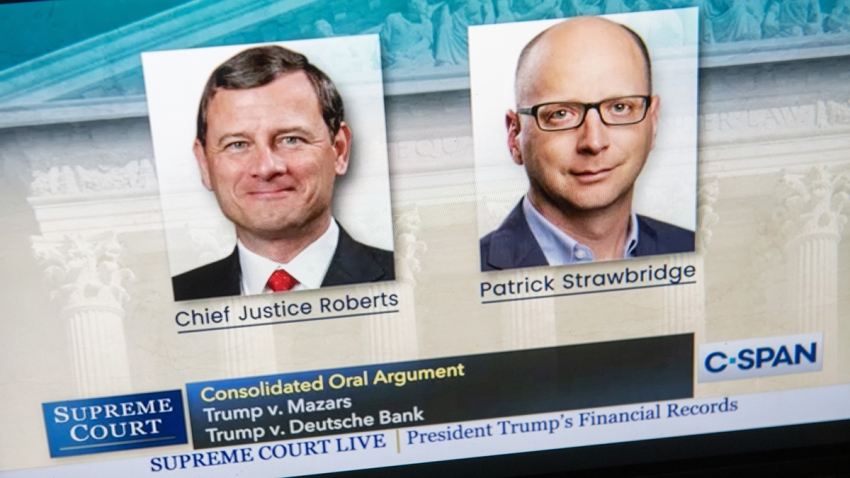 A laptop screen shows still photos of Chief Justice John Roberts and Patrick Strawbridge, an attorney for President Donald Trump, as the Supreme Court convened remotely to hear arguments in two cases dealing with Trump's financial records, May 12, 2020.