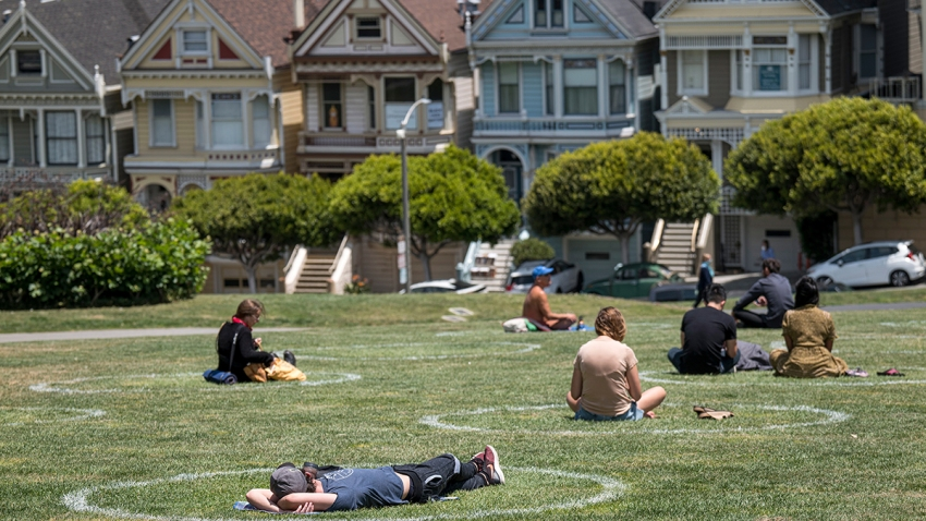 People sit on the grass in circles drawn to promote social distancing at Alamo Square in San Francisco, June 11, 2020.