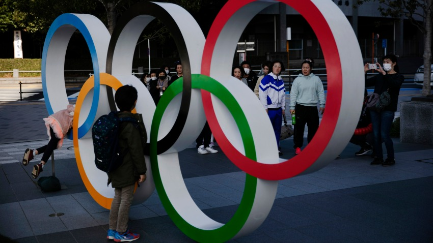 People wait in line to take pictures with the Olympic rings near the New National Stadium, Sunday, Feb. 23, 2020, in Tokyo.