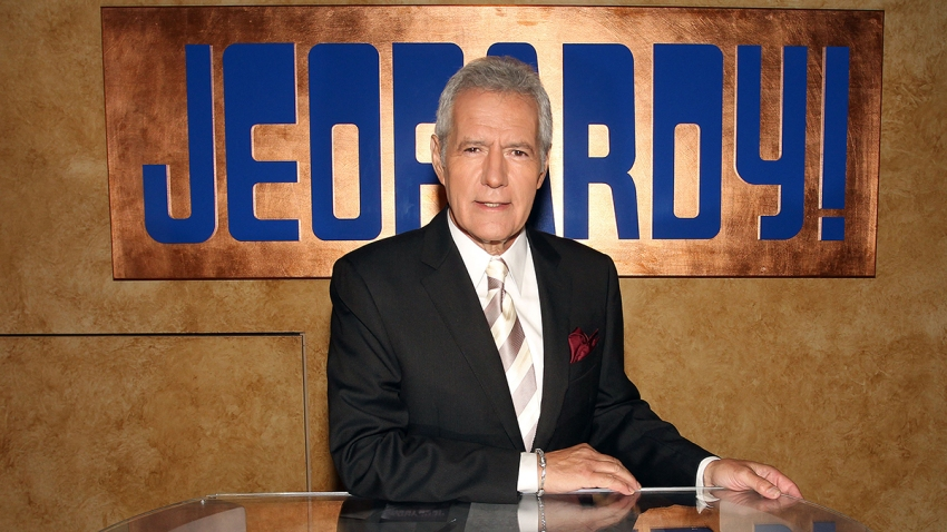 Alex Trebek poses with Jeopardy sign behind him