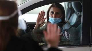 In this Friday, June 26, 2020 photo, U.S. District Judge Laurie Michelson, left, administers the Aath of Citizenship to Hala Baqtar during a drive-thru naturalization service in a parking structure at the U.S. Citizenship and Immigration Services headquarters on Detroit's east side. The ceremony is a way to continue working as the federal courthouse is shut down due to the coronavirus. The U.S. has resumed swearing in new citizens but the oath ceremonies aren't the same because of COVID-19 and a budget crisis at the citizenship agency threatens to stall them again.