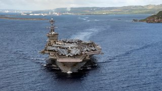 In this June 4, 2020, photo provided by the U.S. Navy, the aircraft carrier USS Theodore Roosevelt (CVN 71) departs Apra Harbor in Guam. The carrier has returned to sea and is conducting military operations in the Pacific region 10 weeks after a massive coronavirus outbreak sidelined the Navy warship.