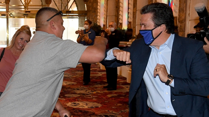 MGM Resorts International Acting CEO and President Bill Hornbuckle (R) bumps elbows with one of the first guests to arrive at Excalibur Hotel & Casino as the Las Vegas Strip property opens for the first time since being closed in mid-March because of the coronavirus pandemic, June 11, 2020, in Las Vegas, Nev.