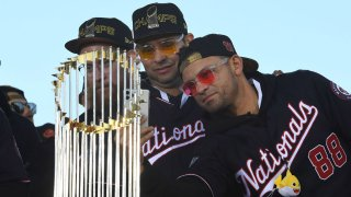 Washington Nationals relief pitcher Sean Doolittle, starting pitcher Anibal Sanchez and center fielder Gerardo Parra take photos in of the commissioner's trophy while on stage at a rally Nov. 2, 2019, in Washington, D.C.