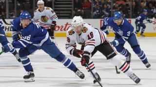 In this Jan. 18, 2020, file photo, Jonathan Toews #19 of the Chicago Blackhawks breaks between Timothy Liljegren #37 and Rasmus Sandin #38 of the Toronto Maple Leafs during an NHL game at Scotiabank Arena in Toronto, Ontario, Canada.